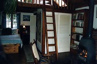 Interior photograph showing fireplace, downstairs bed, and loft